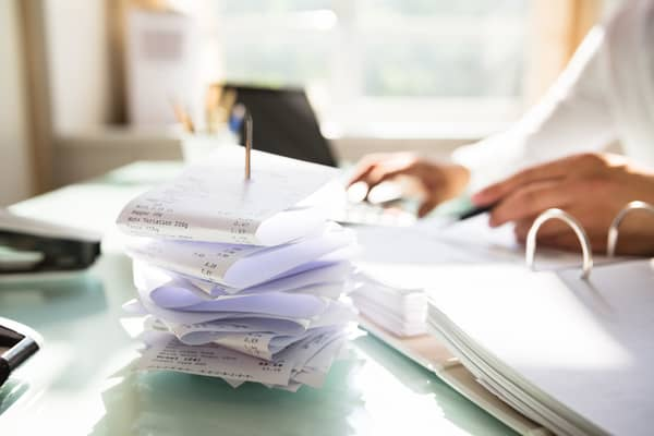 Pile of receipts, woman on computer in background