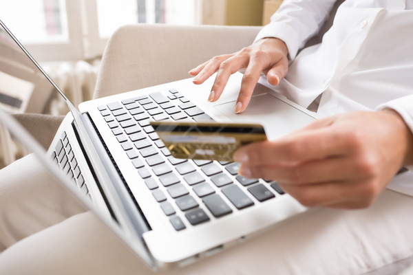 woman holding credit card with laptop to create emergency budget