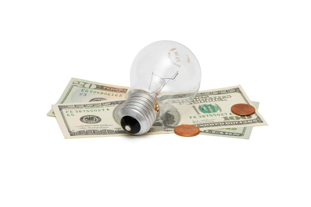 Light bulb on top of money showcasing how to save money on your electric bill