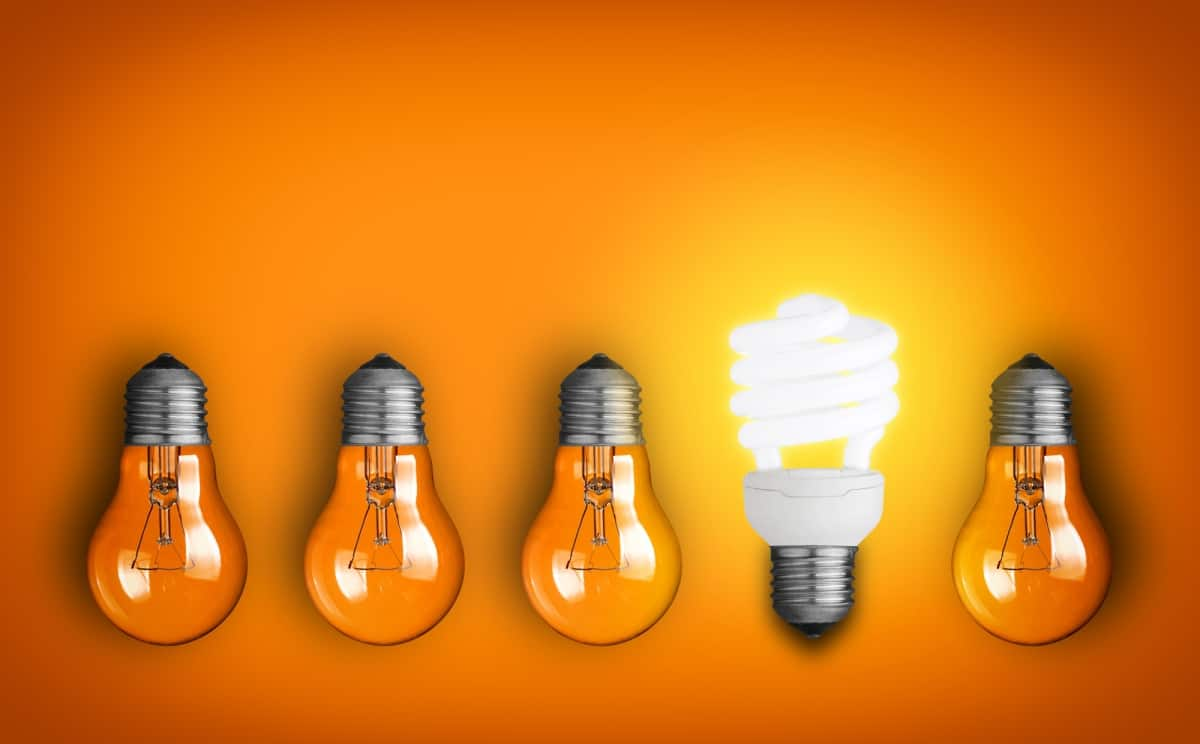 LED light vs incandescent lights on orange background to reinforce that LED lightbulbs lower your electricity bill