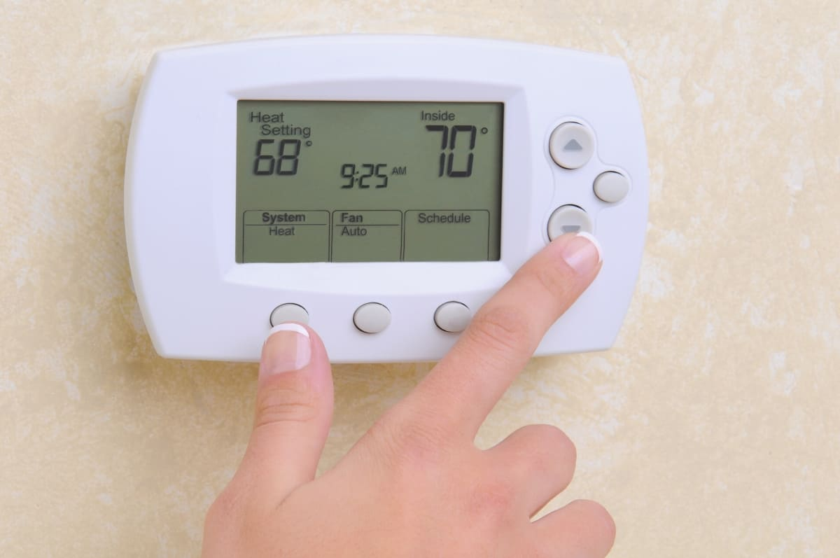 Woman using a thermostat to save money on electric bill